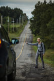 Blonde Woman Hitchhiking on the Side of the Road. And a car Stopping by Royalty Free Stock Photo