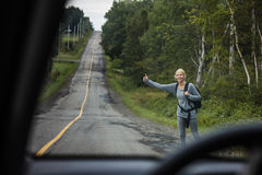 Blonde Woman Hitchhiking. View from Inside a Car of a Blonde Woman Hitchhiking on the Side of the Road Royalty Free Stock Photography