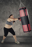 Blonde woman hitting a boxing sack Royalty Free Stock Photography