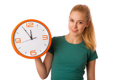 Blonde woman holding big clock in hand isolated over white. Royalty Free Stock Photography