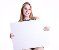Blonde woman holding a blank card isolated on white background Stock Image