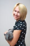 Blonde woman holding a british shorthair male cat Royalty Free Stock Photography