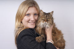 Blonde woman holding brown cat. Blonde woman in black jacket holding brown tabby cat Royalty Free Stock Photo