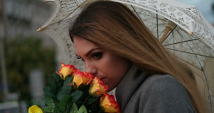Blonde woman holding a bunch of roses in a rainy day walking with the umbrella. Evening time stock video