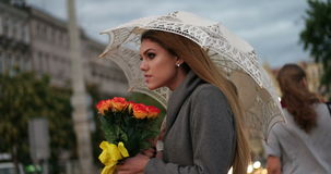 Blonde woman holding a bunch of roses. In a rainy day walking with the umbrella evening time stock video