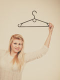 Blonde woman holding clothes hanger Royalty Free Stock Photography
