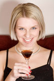 Blonde woman holding a cocktail glass Royalty Free Stock Images