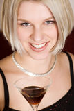 Blonde woman holding a cocktail glass. Young blonde woman holding a cocktail glass Royalty Free Stock Photos
