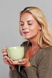 Blonde woman holding a cup of tea and tasting the smell Royalty Free Stock Photography