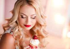 Blonde woman holding cupcake Stock Photography