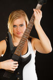 Blonde woman holding electric guitar, black background Stock Photo