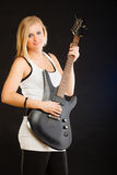 Blonde woman holding electric guitar, black background Royalty Free Stock Image