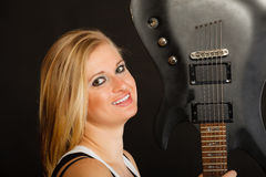 Blonde woman holding electric guitar, black background Royalty Free Stock Images