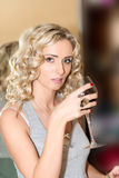 Blonde woman holding a glass of red wine Royalty Free Stock Image