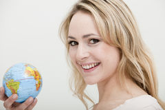 Blonde woman holding a globe Stock Image