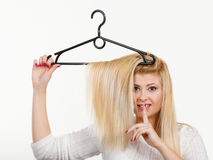 Blonde woman holding hair on clothes hanger Royalty Free Stock Image
