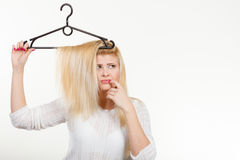 Blonde woman holding hair on clothes hanger Stock Images
