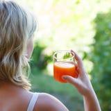 Blonde woman holding juice Stock Photo