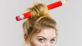 Woman holding magnifying glass having hair pencil Royalty Free Stock Photo