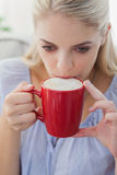Blonde woman holding a mug and sipping from it Royalty Free Stock Photo