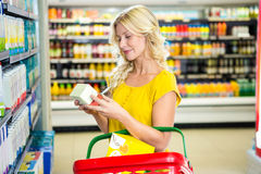 Blonde woman holding product. In supermarket stock photo