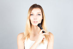 Blonde woman holding professional brush for blush. Make up artist. Stock Photography