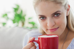 Blonde woman holding a red mug and smiling at camera Stock Image
