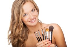 Blonde woman holding set of brushes Stock Images