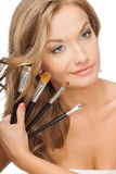 Blonde woman holding set of brushes Stock Photos