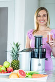 Blonde woman holding a smoothie glass in the kitchen stock photography