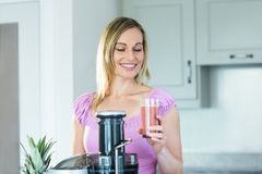 Blonde woman holding a smoothie glass in the kitchen royalty free stock photos