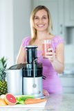 Blonde woman holding a smoothie glass in the kitchen royalty free stock photography