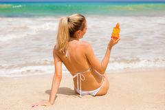 Woman holding sunscreen lotion on the beach. Blonde woman holding sunscreen lotion on the beach Royalty Free Stock Images