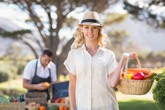 Blonde woman holding a vegetables basket Royalty Free Stock Photos