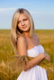 Blonde woman holding wheat sheaf. Outdoors portrait Stock Image