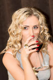 Blonde woman holding a wine Stock Image