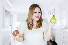Blonde woman holds apple and donut Stock Photo
