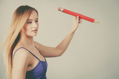 Blonde woman holds big pencil in hand drawing Royalty Free Stock Photo