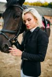 Blonde woman with horse, horseback riding. Portrait of blonde woman with horse, horseback riding. Brown stallion, leisure with animal, equestrian sport Stock Images