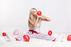 Blonde woman inflating balloons. Blonde young woman sitting on white whole-floor carpet and inflating red balloon stock photo