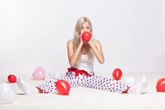 Blonde woman inflating balloons. Blonde young woman sitting on white whole-floor carpet and inflating red balloon Stock Image