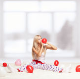 Blonde woman inflating balloons Stock Image