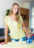 Blonde woman ironing at home Royalty Free Stock Image