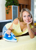 Blonde woman ironing with iron Stock Photo