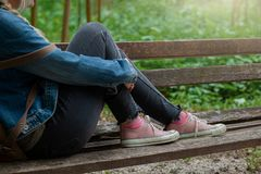 Blonde woman in jeans jacket and pink canvas sneakers sitting on a park bench. Contemplating alone royalty free stock images