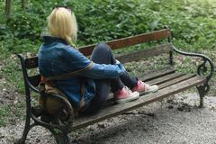Blonde woman in jeans jacket and pink canvas sneakers sitting on a park bench. Contemplating alone stock photos