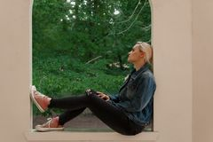 Blonde woman in jeans jacket and pink canvas sneakers sitting on a window still. Green trees in the background, contemplating alone royalty free stock photography