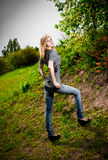 Blonde woman in jeans standing on hill at park Stock Photos