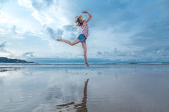Blonde woman jumping over water Stock Photography