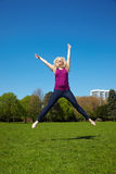 Blonde woman jumping in a park royalty free stock photography
